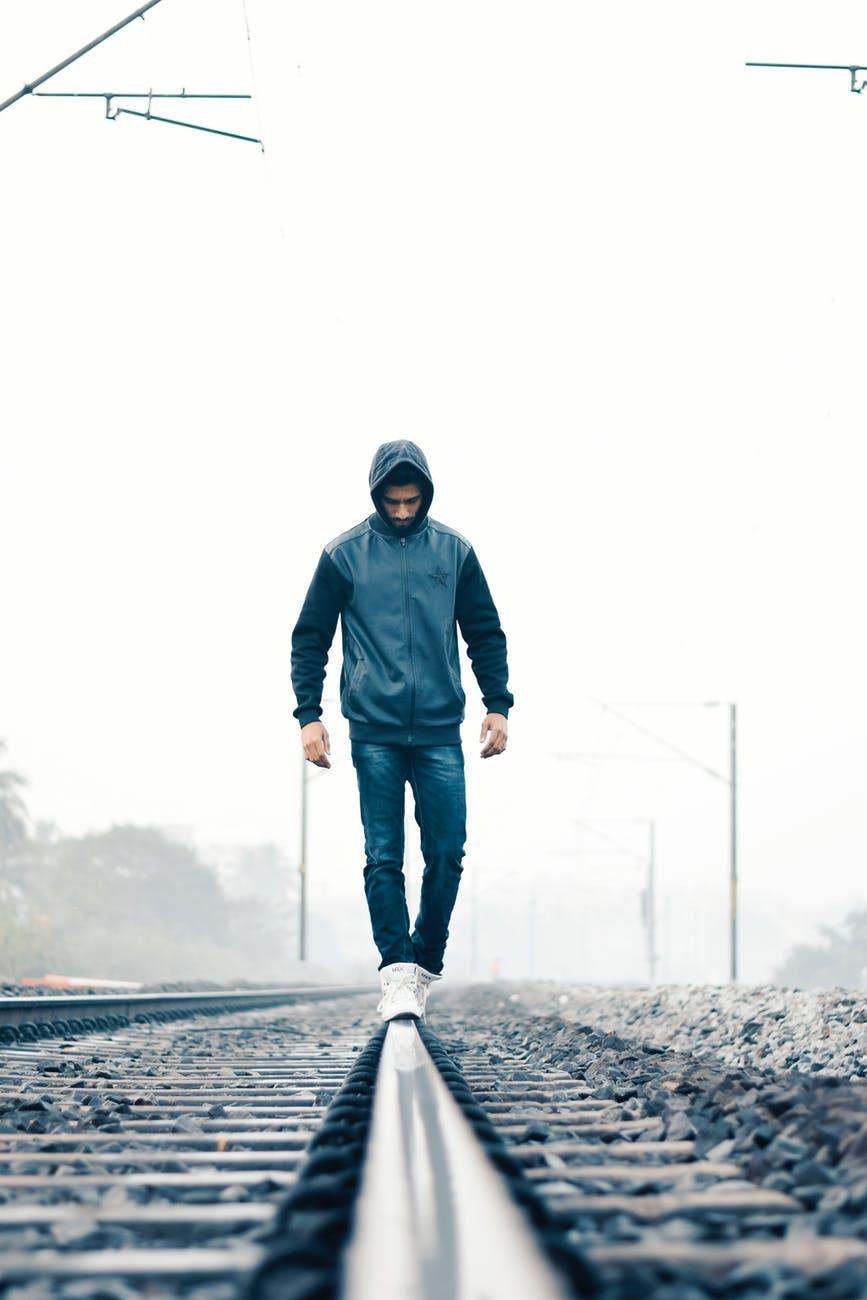 man walking on train rail