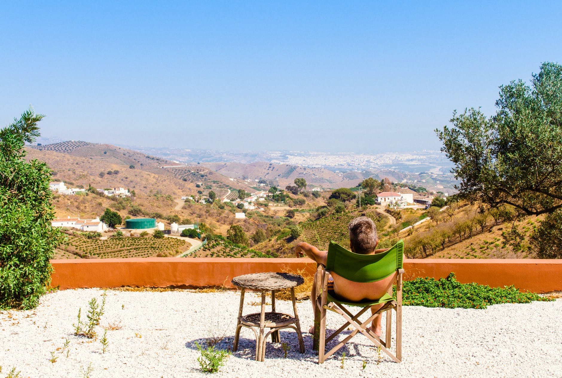 man sitting on green chair near trees and mountain under blue sky at daytime